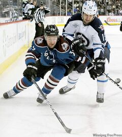Avalanche left-winger T.J. Galiardi (left) and Jets winger Tanner Glass fight for the puck in the first period Tuesday night.