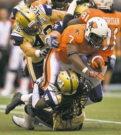 Bombers' Rene Stephan (left) and Alex Suber haul down the Lions' Tim Brown during the Bombers' 27-20 loss to the Lions in Vancouver on Monday.