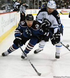 Colorado Avalanche left-winger T.J. Galiardi, left, and Winnipeg Jets' left-wing Tanner Glass fight for the puck in the first period of an NHL hockey game Tuesday in Denver.