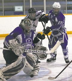 River East Kodiaks goaltender Kristian Strmen follows a bouncing puck as his teammate Tyler Hall battles with  Oak Park Raiders' Grayson Schmidt.