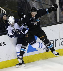 San Jose Sharks' Jason Demers (5) collides against the boards with Winnipeg Jets' Jacob Trouba during the first period Thursday night in San Jose.