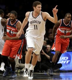 Brooklyn Nets' Brook Lopez points after scoring during the first half of an NBA basketball game against the Washington Wizards on Wednesday, Dec. 18, 2013, in New York. (AP Photo/Seth Wenig)