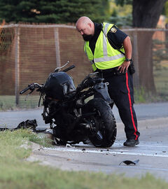A police officer looks over the bike after the driver hit a parked BMW.