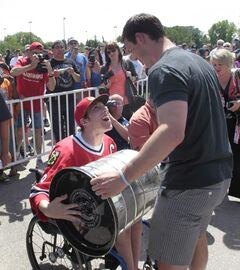 Blackhawks captain Jonathan Toews lets his neighbour, Cameron MacDonald, handle the Stanley Cup outside the Jonathan Toews Community Centre Friday afternoon.