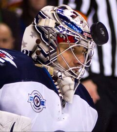 Winnipeg Jets' goalie Ondrej Pavelec watches the puck after it bounces off his mask during the first period of an NHL hockey game against the Vancouver Canucks in Vancouver on Thursday.