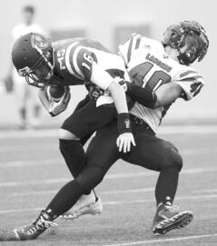 Vincent Massey Trojans quarterback Josh Martin is sacked by Dakota Lancer Derek Dufault.