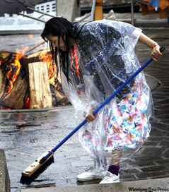 Anne Thomas from Nelson House ignores the rain to sweep around the sacred fire Friday.
