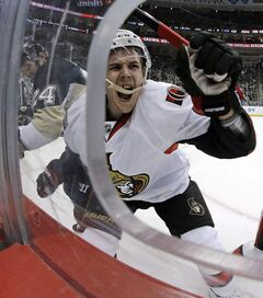 Ottawa Senators defenseman Erik Karlsson, centre, grimaces as he hits the boards after colliding with Pittsburgh Penguins left wing Matt Cooke, left, during game in Pittsburgh on Wednesday, Feb. 13, 2013.