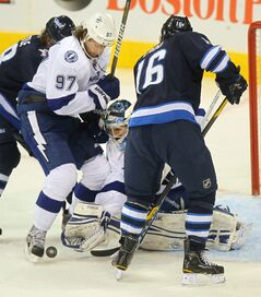 Tampa Bay Lightning netminder Mathieu Garon peers through traffic at the puck while Matt Gilroy (97) and Winnipeg Jet Captain Andrew Ladd battle for possession in the first period at the MTS Centre Thursday.
