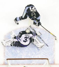 Pittsburgh Penguin Evgeni Malkin swoops around Jets goalie Ondrej Pavelec to light the lamp on Saturday afternoon. Malkin added four assists to the cause in an 8-5 Pens victory.