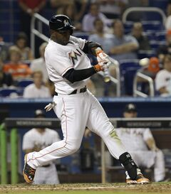 Miami Marlins' Marcell Ozuna connects a single against the Philadelphia Phillies in the fourth inning of a baseball game in Miami, Wednesday, May 21, 2014. Garrett Jones scored on the base hit. (AP Photo/Alan Diaz)