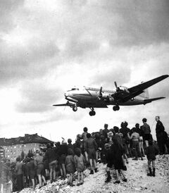 Berliners cheer as a Douglas C-54 flies low over the beleaguered city with a load of supplies.