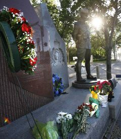 Flowers near  the monument outside the RCMP D Division Headquarters on Portage Avenue commemorate the memory of the three Mounties killed and two others wounded in Moncton, N.B.