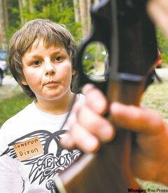 Cameron Dixon, 10, of Fall City, Wash., gets instruction in the use of a rifle from hunter education instructor Bob Cromwell during a hunter education class at the Issaquah Sportsmen's Club in Issaquah, Wash., Thursday Aug. 7, 2008. The class is required to get a hunter's license in the state of Washington.