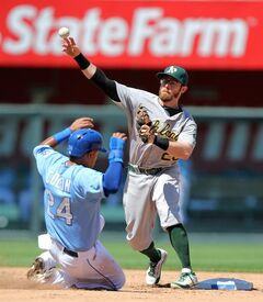 Oakland Athletics' Eric Sogard, back, throws over Kansas City Royals' Christian Colon to first to complete a double play in the fifth inning during a baseball game Thursday, Aug. 14, 2014, in Kansas City, Mo. Norichika Aoki was out at first on the play. (AP Photo/Ed Zurga)