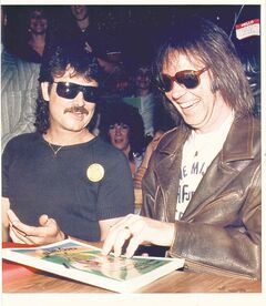 Burton Cummings and Neil Young share a joke while signing books at the Paddlewheel Restaurant.