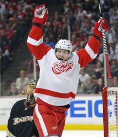 FILE - In this March 24, 2013 file photo, Detroit Red Wings right wing Daniel Cleary, right, celebrates his goal as Anaheim Ducks goalie Jonas Hiller, rear, of Switzerland, kneels, during the first period of their NHL hockey game in Anaheim. The Detroit Red Wings have re-signed left wing Daniel Cleary to a one-year contract. THE CANADIAN PRESS/AP, Mark J. Terrill