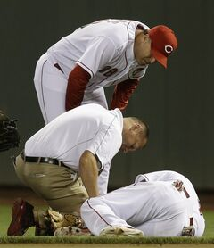 Cincinnati Reds second baseman Brandon Phillips is checked by trainer Steve Bauman, center, and manager Bryan Price, top, after Phillips was injured in the eighth inning of a baseball game against the Chicago Cubs, Wednesday, July 9, 2014, in Cincinnati. Phillips was taken out of the game won by Cincinnati 4-1. (AP Photo/Al Behrman)