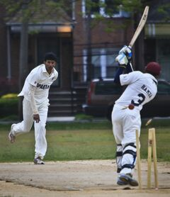 In this May 12, 2014 photo, John Adams High School batsman and bowler Derick Narine, left, bowls out Midwood High School batsman Hamza Khushnud, taking a wicket, during a Public School Athletic League cricket match, at Marine Park in the Brooklyn borough of New York. Narine, a junior from Guyana and a member of its under-19 national squad, dismissed three opponents in his first four balls bowled, contributing fast paced bowling along with over 50 runs at bat in a 112-80 win. (AP Photo/Bebeto Matthews)