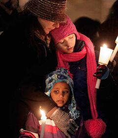 A woman comforts children at a vigil for six-year-old Ana Grace Marguez-Greene — one of the Newtown, Conn., shooting victims — at the University of Winnipeg on Monday. Ana's mother taught at the University of Winnipeg and her father taught at the University of Manitoba before moving to Newtown this past July.