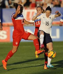 United States' Carli Lloyd, left, and Allie Long, center, pressure France's Elise Bussaglia, right, during the first half of a women's friendly soccer match on Thursday, June 19, 2014, in East Hartford, Conn. (AP Photo/Jessica Hill)