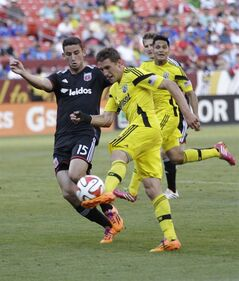 RETRANSMISSION TO CORRECT YEAR - Columbus Crew's Ethan Finlay, right, kicks the ball as D.C. United's Steven Birnbaum (15) defends during the first half of an MLS soccer game, Saturday, June 7, 2014, in Landover, Md. (AP Photo/Luis M. Alvarez)