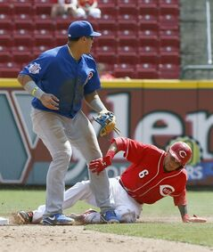 Cincinnati Reds' Billy Hamilton, right, is safe at second after an error by Chicago Cubs second baseman Javier Baez, left, in the sixth inning of a baseball game, Thursday, Aug. 28, 2014, in Cincinnati. The Reds won 7-2. (AP Photo/David Kohl)