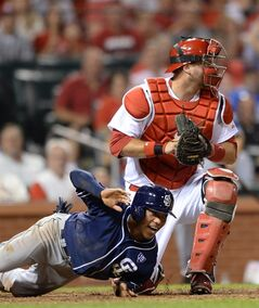 St. Louis Cardinals' A.J. Pierzynski, right, looks for the call at home after tagging San Diego Padres' Alexi Amarista, left, in the ninth inning in a baseball game, Thursday, Aug. 14, 2014, at Busch Stadium in St. Louis. (AP Photo/Bill Boyce)