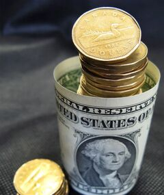 Canadian loonies are pictured with U.S dollars in this April 6, 2010 photo. THE CANADIAN PRESS/Ryan Remiorz