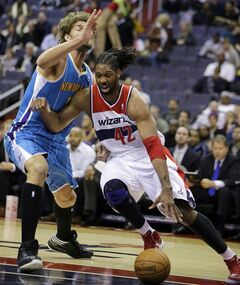 Washington Wizards center Nene (42), from Brazil, dribbles past New Orleans Hornets center Robin Lopez (15) in the first half of an NBA basketball game Friday, March 15, 2013 in Washington. (AP Photo/Alex Brandon)
