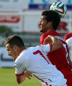 Iran's Masoud Shojaei, right, with Marko Vesovic, left, of Montenegro during a friendly soccer match between Iran and Montenegro, in Hartberg, Austria, Monday, May 26, 2014. (AP Photo/Ronald Zak)