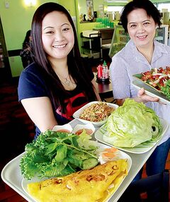 Left, Lisa Dang (with a tray of Vietnamese crepe and the chicken lettuce wrap) and her mother Trinh Nguyen, (holding plates of fried chicken, crispy ginger beef, kung pao chicken and sesame chicken) in their family run Pembina Highway restaurant.