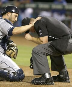 Cleveland Indians catcher George Kottaras, left, checks on home plate umpire Jim Wolf after Wolf was hit by a pitch during the sixth inning of a baseball game in Arlington, Texas, Monday, June 9, 2014. Wolf left the game. (AP Photo/LM Otero)