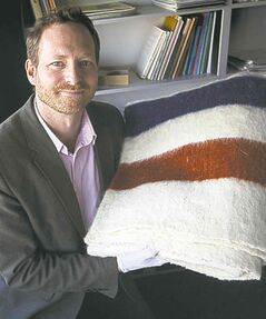 Manitoba Museum curator Roland Sawatzky with the distinctive Hudson's Bay Company blanket owned by Cuthbert Grant.