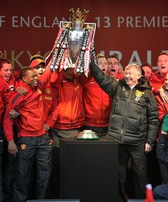 Manchester United's Alex Ferguson, right, lifts the Premier League trophy with Patrice Evra, left, during their premiership trophy parade, after winning the English Premier League, in Manchester, England, Monday May 13, 2013. Manager Alex Ferguson has retired after more than 26 years in charge at the club. (AP Photo/Clint Hughes)