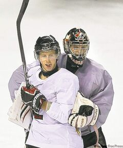 Canada's Cody Eakin pals around with goalie Mark Visentin Monday in Buffalo.