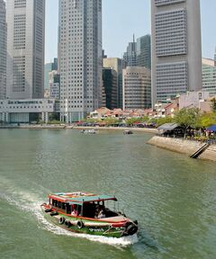 A passenger bumboat travels in front of the Singapore Financial District.