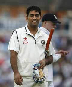 India's MS Dhoni smiles as he walks off the pitch for the tea interval as he plays against England during the first day of the fifth test cricket match at Oval cricket ground in London, Friday, Aug. 15, 2014. (AP Photo/Alastair Grant)