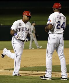 Texas Rangers' Adrian Beltre is congratulated as he rounds third by base coach Gary Pettis (24) following Beltre's solo home run off of Oakland Athletics relief pitcher Evan Scribner in the eighth inning of a baseball game, Sunday, July 27, 2014, in Arlington, Texas. The shot was Beltre's 391st career home run. (AP Photo/Tony Gutierrez)
