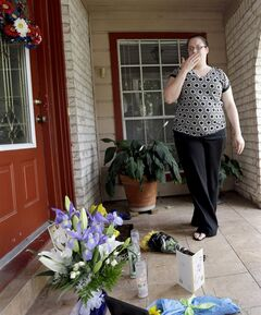 Neighbor Kristen Breelove pauses after leaving flowers on the porch of a home Thursday, July 10, 2014, in Spring, Texas. where six family members were shot to death the night before. he Harris County Sheriff's Office says Ronald Lee Haskell was booked Thursday on a capital murder/multiple murders charge and held without bond. Authorities believe Haskell fatally shot two adults and four children on Wednesday night and critically wounded a 15-year-old girl, who called 911. (AP Photo/David J. Phillip)