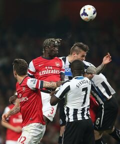 Arsenal's Bacary Sagna, top left heads the ball towards goal during their English Premier League soccer match between Arsenal and Newcastle United at the Emirates stadium in London, Monday, April 28, 2014. (AP Photo/Alastair Grant)