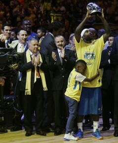 Maccabi Tel Aviv's Tyrese Rice holds the trophy as a best player as he is hugged by his son at the end of the Euroleague Final Four final match against Real Madrid in Milan, Italy, Sunday, May 18, 2014. (AP Photo/Luca Bruno)