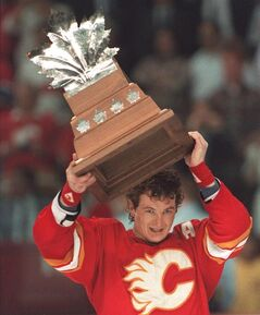 Calgary Flames' Al MacInnis hoists the Conn Smythe Trophy as playoff MVP after the Flames beat the Montreal Canadiens to win the Stanley Cup in Montreal, May 26, 1989. MacInnis is set to be honoured with a banner in the rafters at the Saddledome.The Calgary Flames announced Wednesday that the former defenceman will be feted on Feb. 27 prior to a game against the St. Louis Blues. THE CANADIAN PRESS/Ryan Remiorz