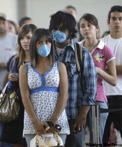 Miranda Carnewro, 18, and Jorge Juarez, 18, wear masks as they wait to clear U.S. Customs crossing from Ciudad Juarez, Mexico, into El Paso, Texas.