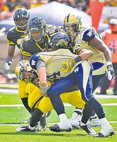 Bombers quarterback Buck Pierce (front) gets sacked by Tiger-Cats.