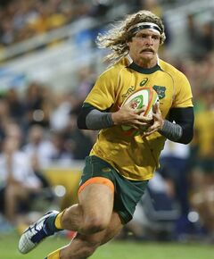 Australian left wing Nick Cummins runs in to score a try during their Rugby test match against France in Brisbane, Australia, Saturday, June 7, 2014. (AP Photo/Tertius Pickard)