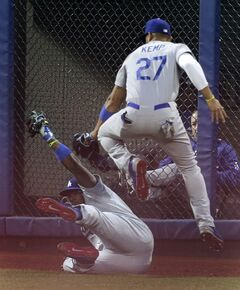 Los Angeles Dodgers center fielder Matt Kemp (27) leaps over right fielder Yasiel Puig (66) as Puig holds up a diving catch on a ball hit by New York Mets' Wilmer Flores during the second inning of a baseball game, Thursday, May 22, 2014, in New York. (AP Photo/Julie Jacobson)
