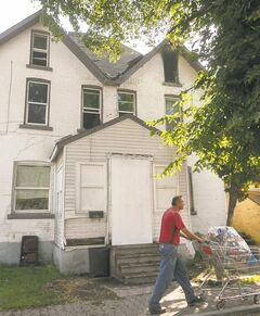 A man passes 145 Euclid Ave the morning after a fire in the rooming house caused an estimated $450,000 in damages.