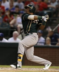 Oakland Athletics' Yoenis Cespedes follows through on a solo home run off a pitch from Texas Rangers starting pitcher Nick Tepesch in the sixth inning of a baseball game on Saturday, July 26, 2014, in Arlington, Texas. (AP Photo/Tony Gutierrez)
