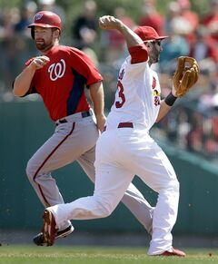 St. Louis Cardinals second baseman Daniel Descalso, right, completes the double play by throwing out Washington Nationals' Chris Marrero at first as the Nationals' Chad Tracy, left, is called out for running outside the base path during the second inning of an exhibition spring training baseball game Friday, March 15, 2013, in Jupiter, Fla. (AP Photo/Jeff Roberson)